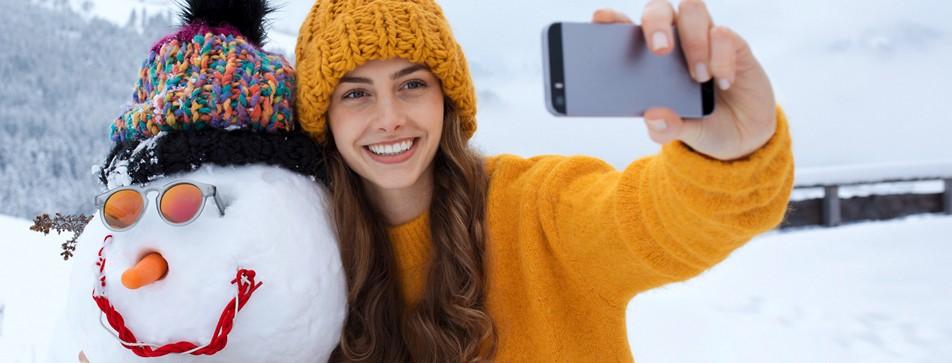Junge Frau mit Haube macht ein Selfie von ihr und einem Schneemann.