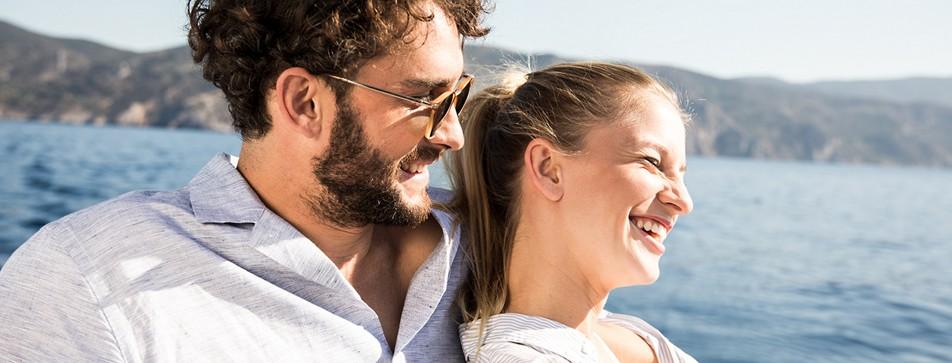 Ein junges Paar, das gemeinsam ins Meer blickt