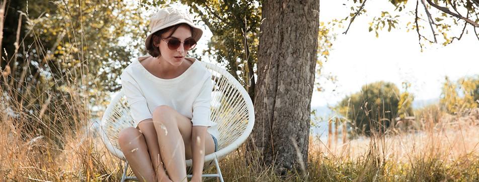 Junge Frau sitzt auf einem Sessel mitten in der Natur.
