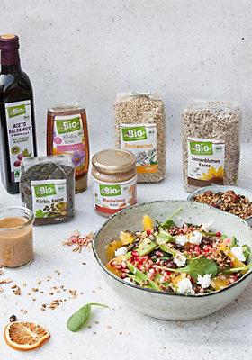 Schüssel mit Avocado-Granatapfel-Salat mit den Zutaten von dmBio im Hintergrund.