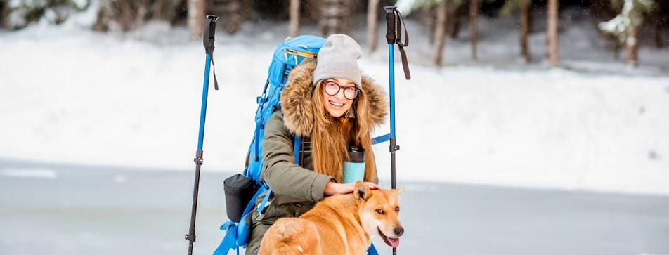 Junge Frau mit Hund beim Winterwandern