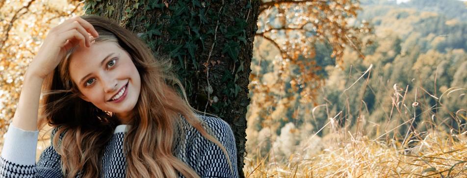 Frau lehnt am Baum und streicht sich durch die Haare