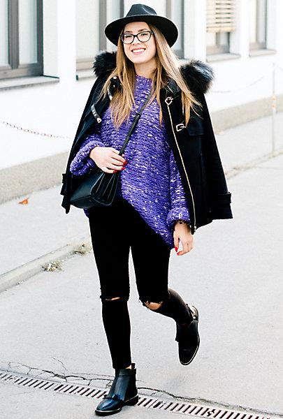 Nikolina trägt im Street Style eine schwarze Hose, einen lila Wollpulli und eine schwarze Jacke.