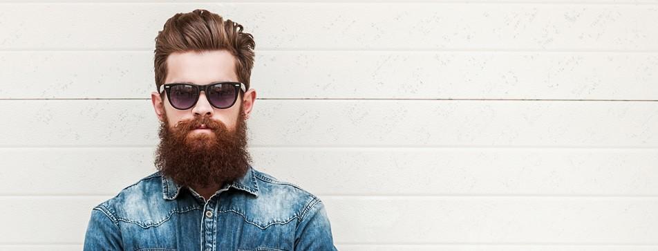 Hipster mit Vollbart, Sonnenbrille und Jeanshemd.