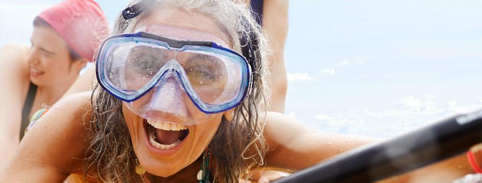 Frau mit nassen Haaren, Taucherbrille und Paddel.