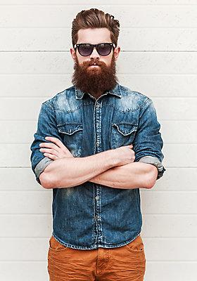 Mann mit Vollbart, Sonnenbrille und Jeanshemd.