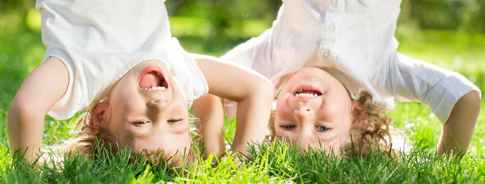 Zwei Kleinkinder machen einen Kopfstand in der Wiese