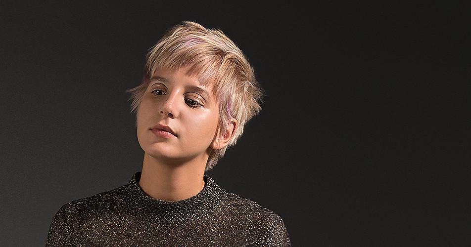 Frau mit einem modernen, blonden Kurzhaarschnitt.