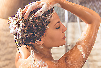 Frau wäscht sich die Haare mit dem NIVEA Mizellenshampoo