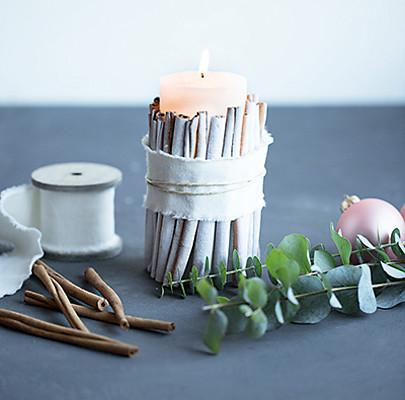 Ein Band wird um die Kerze und die Zimtstangen gewickelt